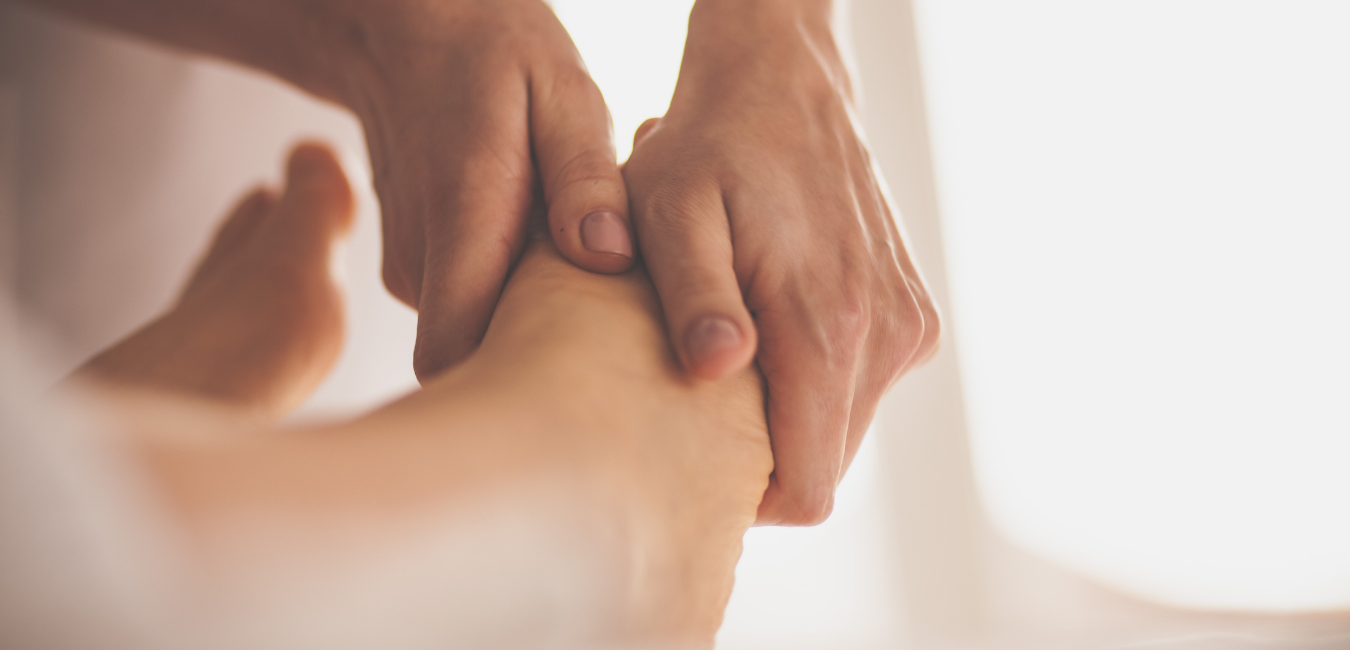 Two hands massage a foot during an in-home massage